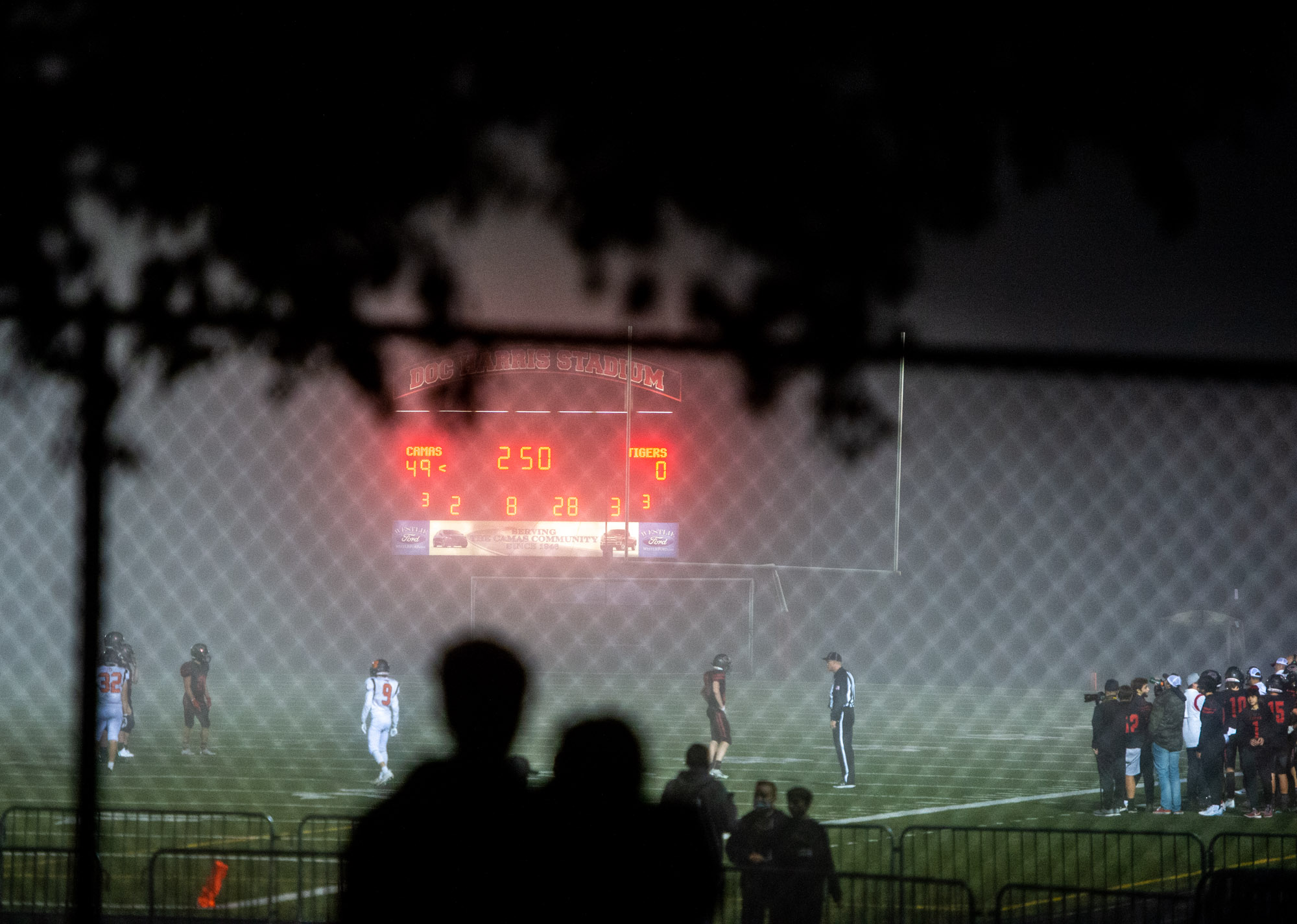 A couple snuggles up outside the stadium fencing to watch the third quarter in a 4A Greater St. Helens League football game on Thursday, Sept. 30, 2021, at Doc Harris Stadium in Camas. Camas won 56-6 over Battle Ground.