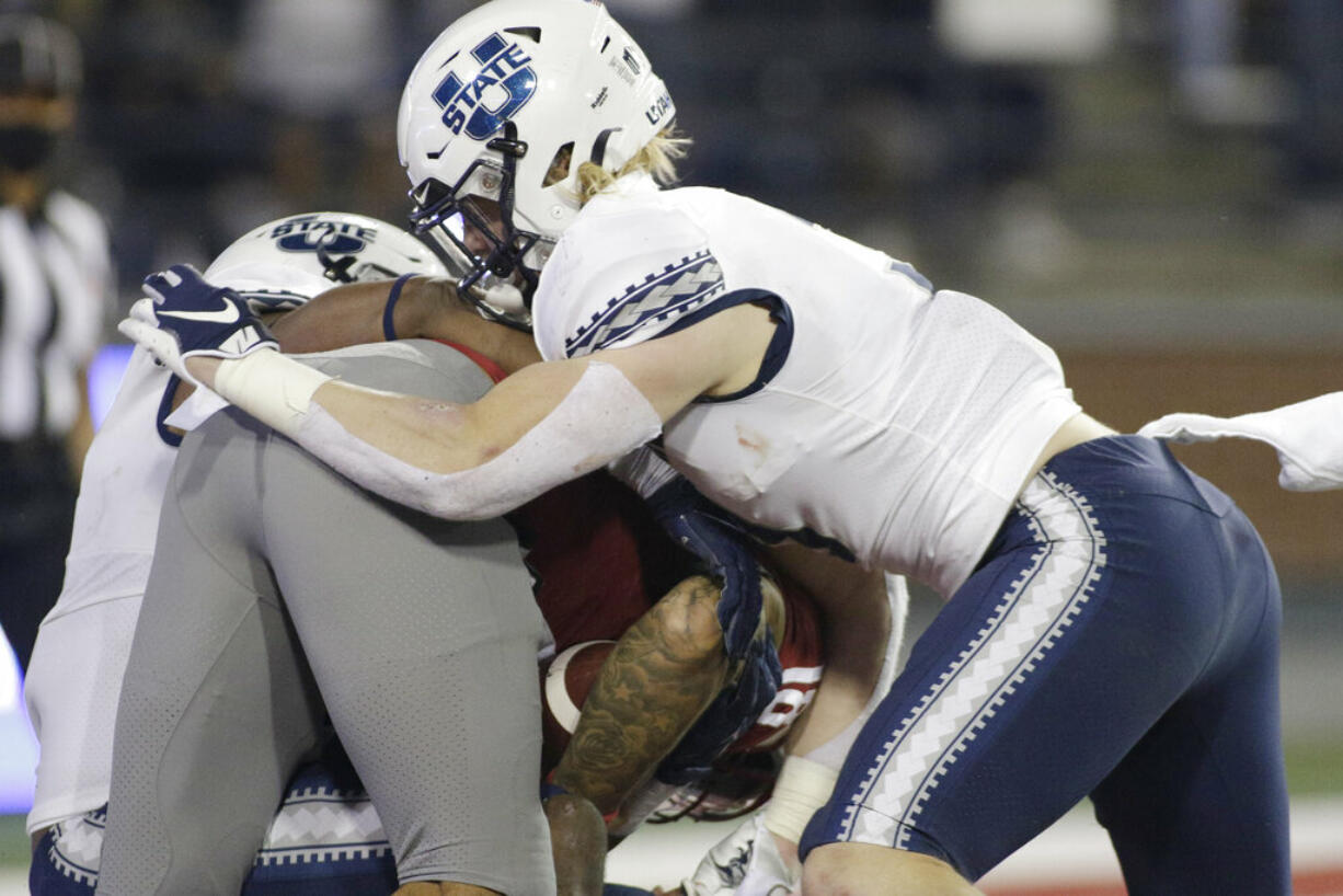 Utah State defensive end Patrick Joyner Jr., left, and linebacker Justin Rice, right, tackle Washington State quarterback Jarrett Guarantano for a safety during the first half of an NCAA college football game Saturday, Sept. 4, 2021, in Pullman, Wash.