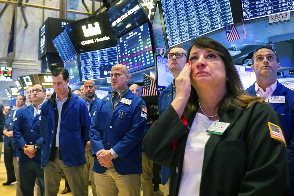 In this photo provided by the New York Stock Exchange, floor traders, including Phyllis Arena Woods, right, gather in remembrance on the eve of September 11th, on the Exchange trading floor, Friday Sept. 10, 2021.