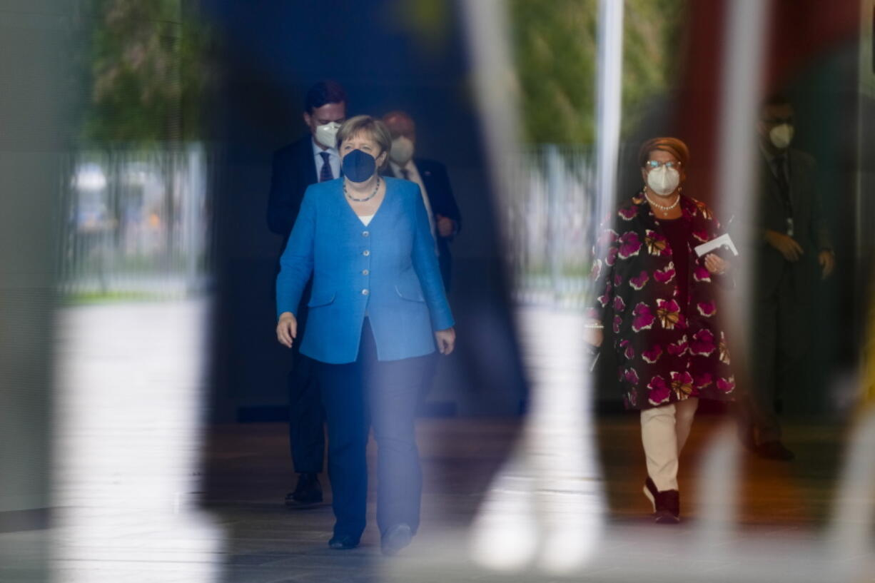 German Chancellor Angela Merkel walks through the chancellery on her way to welcome Lithuania's President Gitanas Nauseda for a meeting in Berlin, Germany, Thursday, Sept. 16, 2021.