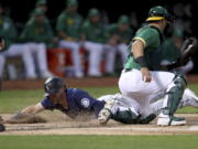 Seattle Mariners' Jake Bauers slides home safe on a throwing error by Paul Blackburn as Oakland Athletics' Yan Gomes applies the tag during the second inning of a baseball game in Oakland, Calif., Tuesday, Sept. 21, 2021.