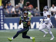 Seattle Seahawks wide receiver Tyler Lockett (16) catches a pass before running for a touchdown in from of Tennessee Titans strong safety Bradley McDougald, right, during the first half of an NFL football game, Sunday, Sept. 19, 2021, in Seattle.