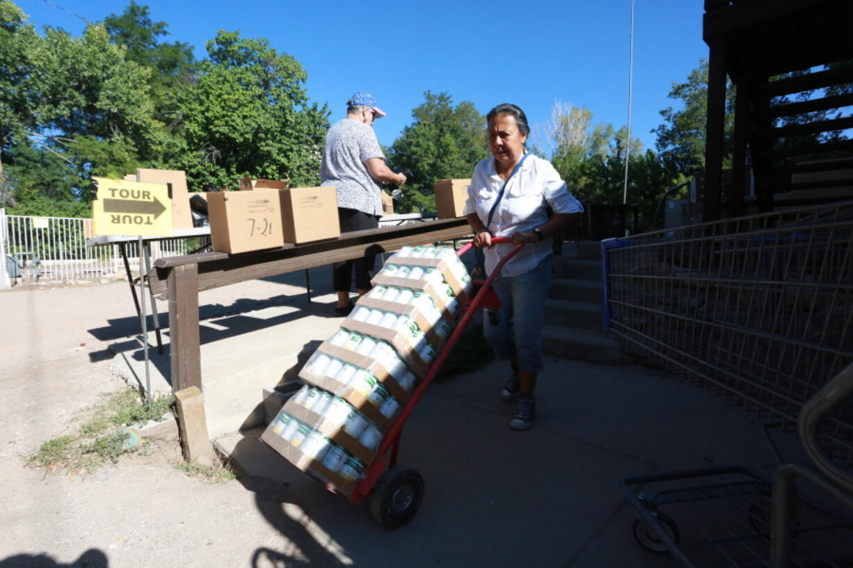 Barrios Unidos president Lupe Salazar pushes a dolly filled with canned food ahead of a food drive on Thursday, Sept. 23, 2021, in Chimay?, New Mexico.