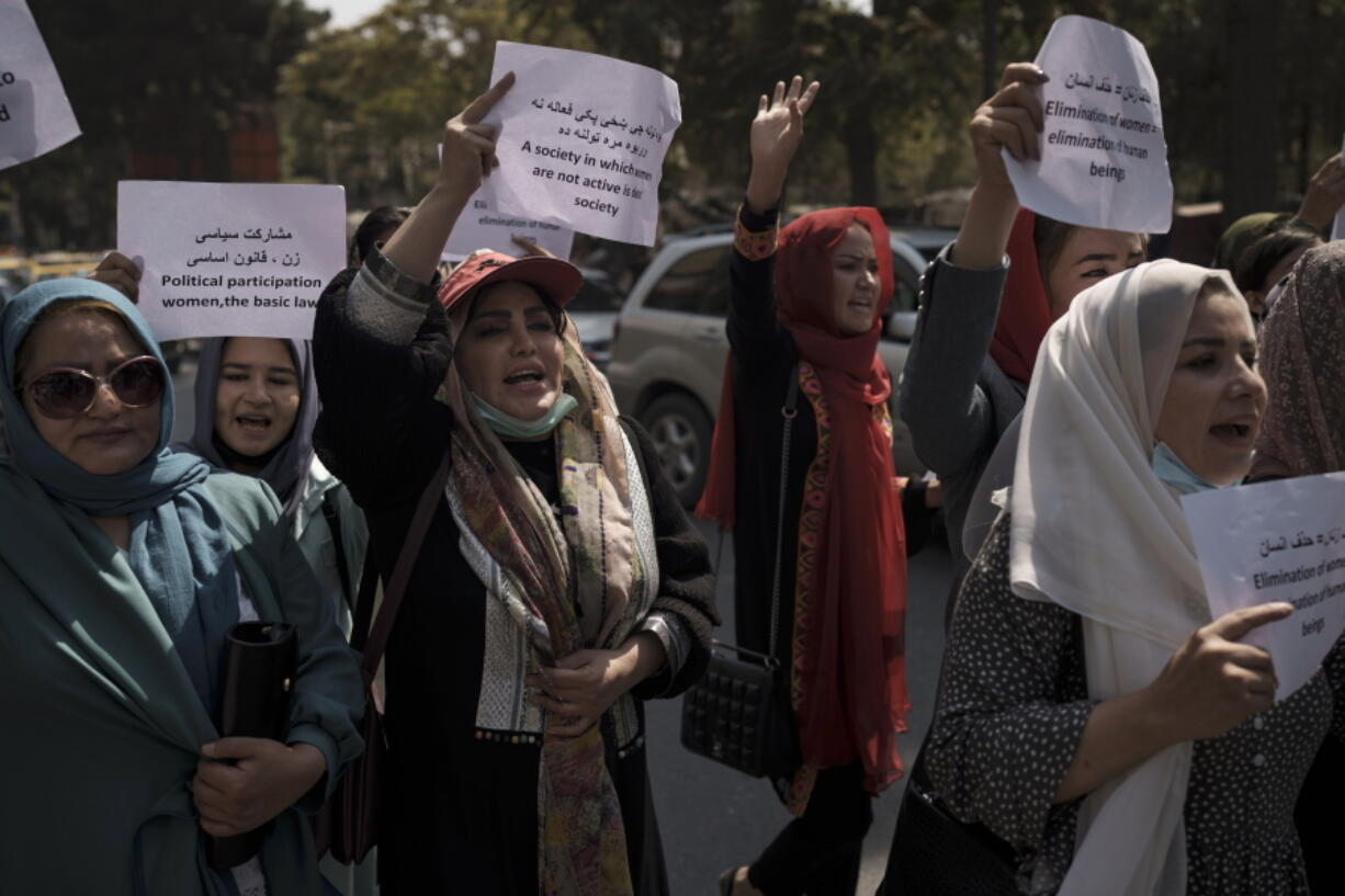 Women march to demand their rights under the Taliban rule during a demonstration near the former Women's Affairs Ministry building in Kabul, Afghanistan, Sunday, Sept. 19, 2021. The interim mayor of Afghanistan's capital said Sunday that many female city employees have been ordered to stay home by the country's new Taliban rulers.