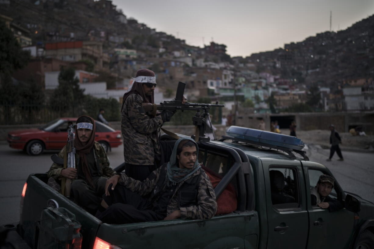 Taliban fighters sit on the back of a pickup truck as they stop on a hillside in Kabul, Afghanistan, Sunday, Sept. 19, 2021.
