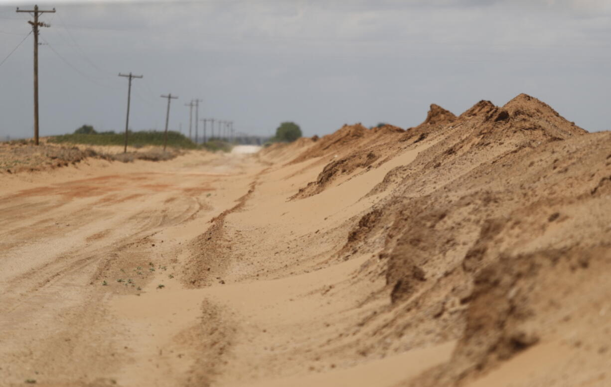 """Sand that blew off farmers' fields is piled up in a ditch outside Lingo, N.M., near the Texas-New Mexico border on Tuesday, May 18, 2021. The U.S. Department of Agriculture is encouraging farmers in a """"Dust Bowl zone"""" that includes parts of Texas, New Mexico, Oklahoma, Kansas and Colorado to establish and preserve grasslands to prevent wind erosion as the area becomes increasingly dry."""