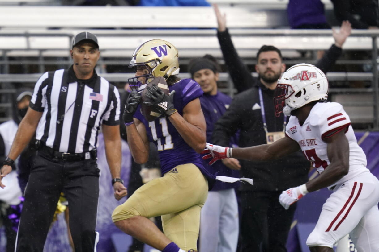 Washington's Jalen McMillan (11) scores on a 33-yard pass reception as Arkansas State's Denzel Blackwell defends in the first half of an NCAA college football game, Saturday, Sept. 18, 2021, in Seattle.