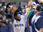 Seattle Mariners' J.P. Crawford is congratulated by teammates after scoring against the Houston Astros during the sixth inning of a baseball game Wednesday, Sept. 1, 2021, in Seattle.