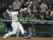 Seattle Mariners' Ty France hits a sacrifice fly to score Dylan Moore during the seventh inning of a baseball game against the Oakland Athletics, Wednesday, Sept. 29, 2021, in Seattle. (AP Photo/Ted S.