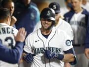 Seattle Mariners' Mitch Haniger celebrates in the dugout after hitting a solo home run in the seventh inning of a baseball game against the Oakland Athletics Tuesday, Sept. 28, 2021, in Seattle.