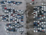 FILE - In this March 24, 2021 file photo, mid-sized pickup trucks and full-size vans are seen in a parking lot outside a General Motors assembly plant where they are produced in Wentzville, Mo. The global shortage of computer chips is getting worse, forcing automakers to temporarily close factories including those that build popular pickup trucks. General Motors announced Thursday, Sept, 2, 2021 that it would pause production at seven North American plants during the next two weeks, including two that make the company's top-selling Chevrolet Silverado pickup.
