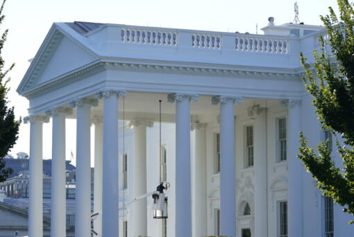 A worker works on the light fixture over the North Portico of the White House in Washington, Friday, Sept. 3, 2021.