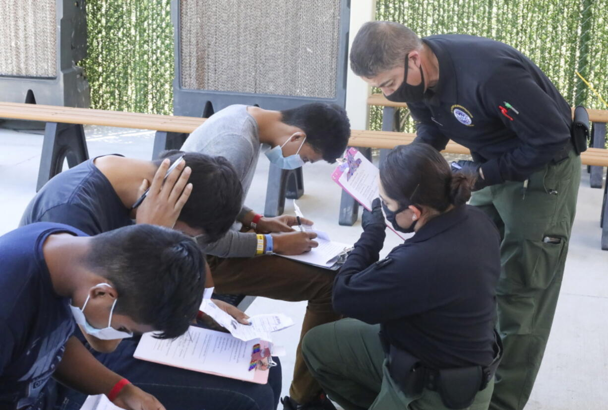 This May 4, 2021, photo provided by The U.S. Border Patrol shows U.S. Border Patrol Processing Coordinators assisting in the processing of underage migrant children at the entrance of the Central Processing Center in El Paso, Texas. The Border Patrol says agents spend about 40% of their time on custody care and administrative tasks that are unrelated to border security, creating a staffing challenge. (U.S.