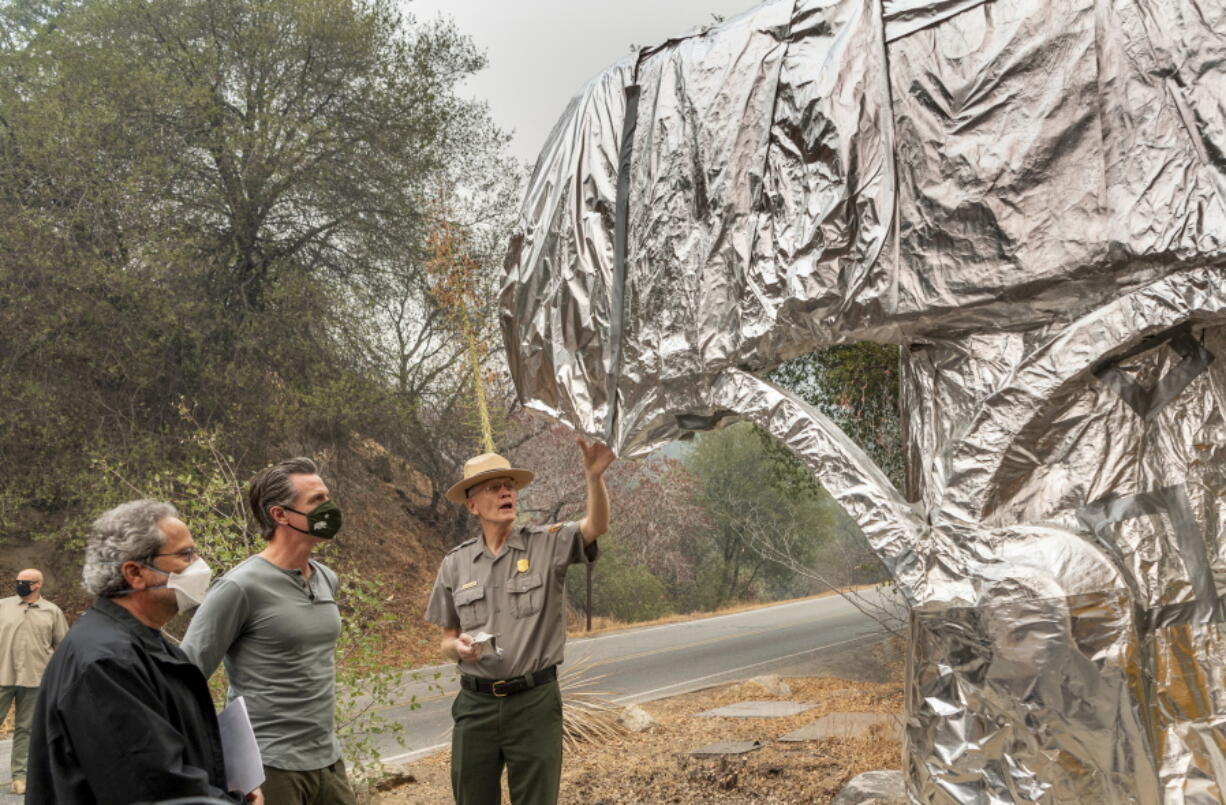 State Assembly Member Richard Bloom, D-Santa Monica, left, and California Gov. Gavin Newsom, second left, listen to Superintendent of Sequoia and Kings Canyon National Parks Clay Jordan, right, talk about the protective structure wrap used to protect the welcome sign and giant sequoia trees from the KNP Complex Fire, on Thursday, Sept. 23, 2021, in Sequoia National Park, Calif. Newsom on Thursday approved nearly $1 billion in new spending to prevent wildfires, signaling a policy shift in a state that historically focused more on putting out fires than stopping them before they start.
