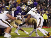 Washington's Sean McGrew (5) scores against California in the second quarter to put the Huskies on top 21-7. Much later, McGrew scored the go-ahead touchdown in overtime as UW won its Pac-12 Conference opener Saturday.