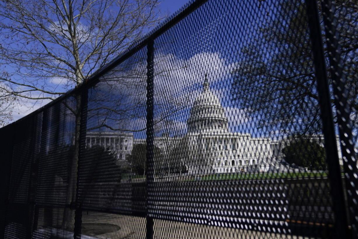FILE - In this April 2, 2021, file photo, the U.S. Capitol is seen behind security fencing on Capitol Hill in Washington. Law enforcement concerned by the prospect for violence at a rally in the nation's Capitol next week are planning to reinstall protective fencing that surrounded the U.S. Capitol for months after the Jan. 6 insurrection there, according to a person familiar with the discussions.