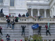 """FILE - In this Jan. 6, 2021 file photo, rioters climb the west wall of the the U.S. Capitol in Washington. First, some blamed the deadly Jan. 6 attack on the Capitol on left-wing Antifa antagonists, a theory quickly debunked. Then came comparisons of the rioters as peaceful protesters, or even """"tourists."""" Now, Trump allies rallying in support of those people charged in the Capitol riot are calling them """"political prisoners,"""" a stunning effort to revise the narrative of that deadly day."""