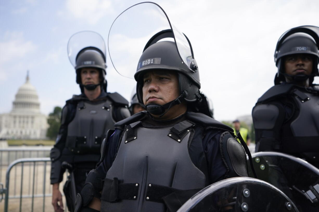 """Police in riot gear patrol as people attend a rally near the U.S. Capitol in Washington, Saturday, Sept. 18, 2021. The rally was planned by allies of former President Donald Trump and aimed at supporting the so-called """"political prisoners"""" of the Jan. 6 insurrection at the U.S. Capitol."""