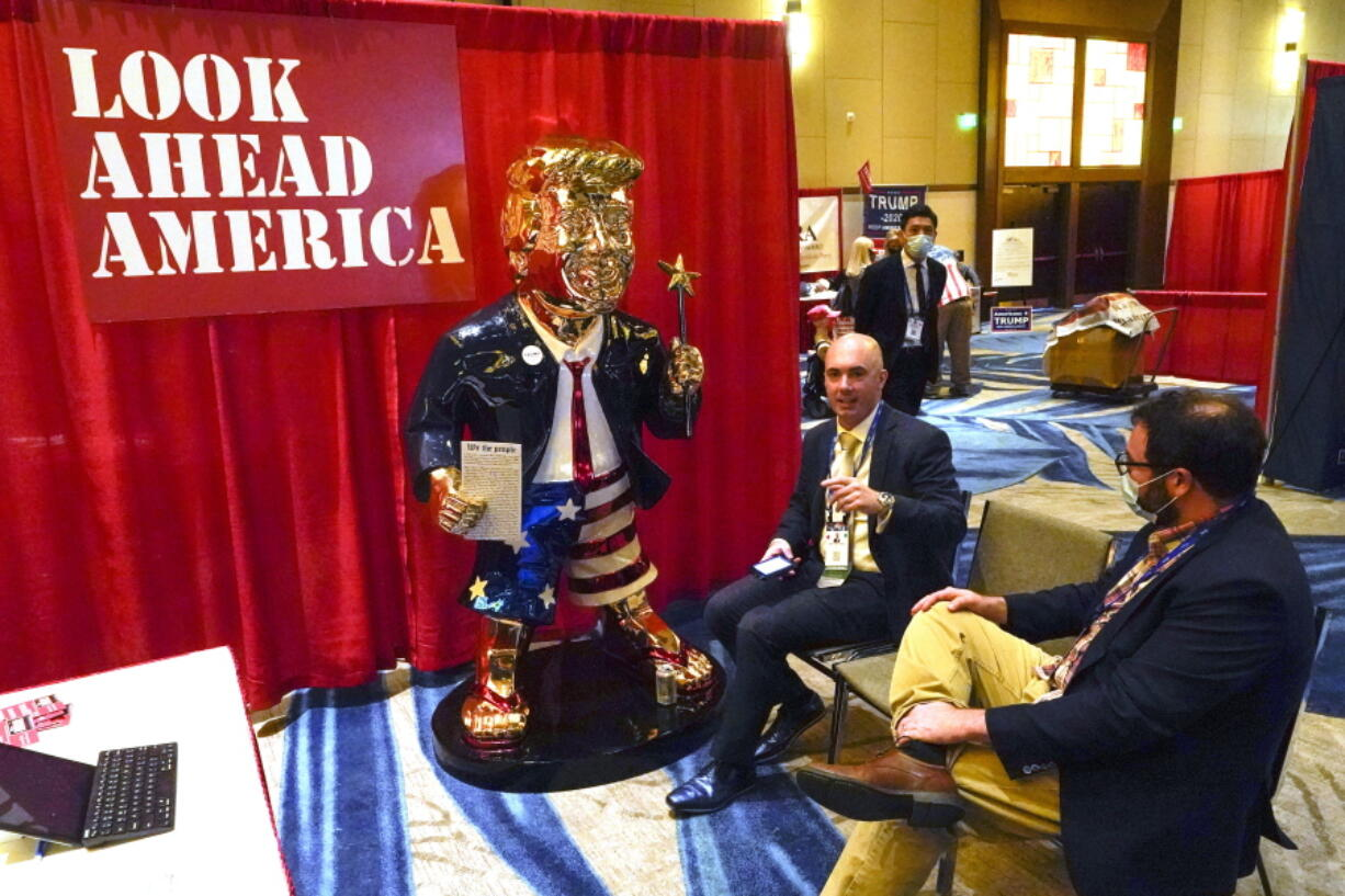 FILE - In this Feb. 26, 2021, file photo, Look Ahead America sponsor Matt Braynard, center, talks to conference attendees at his booth in the merchandise show with a statue of former president Donald Trump at the Conservative Political Action Conference (CPAC) in Orlando, Fla.