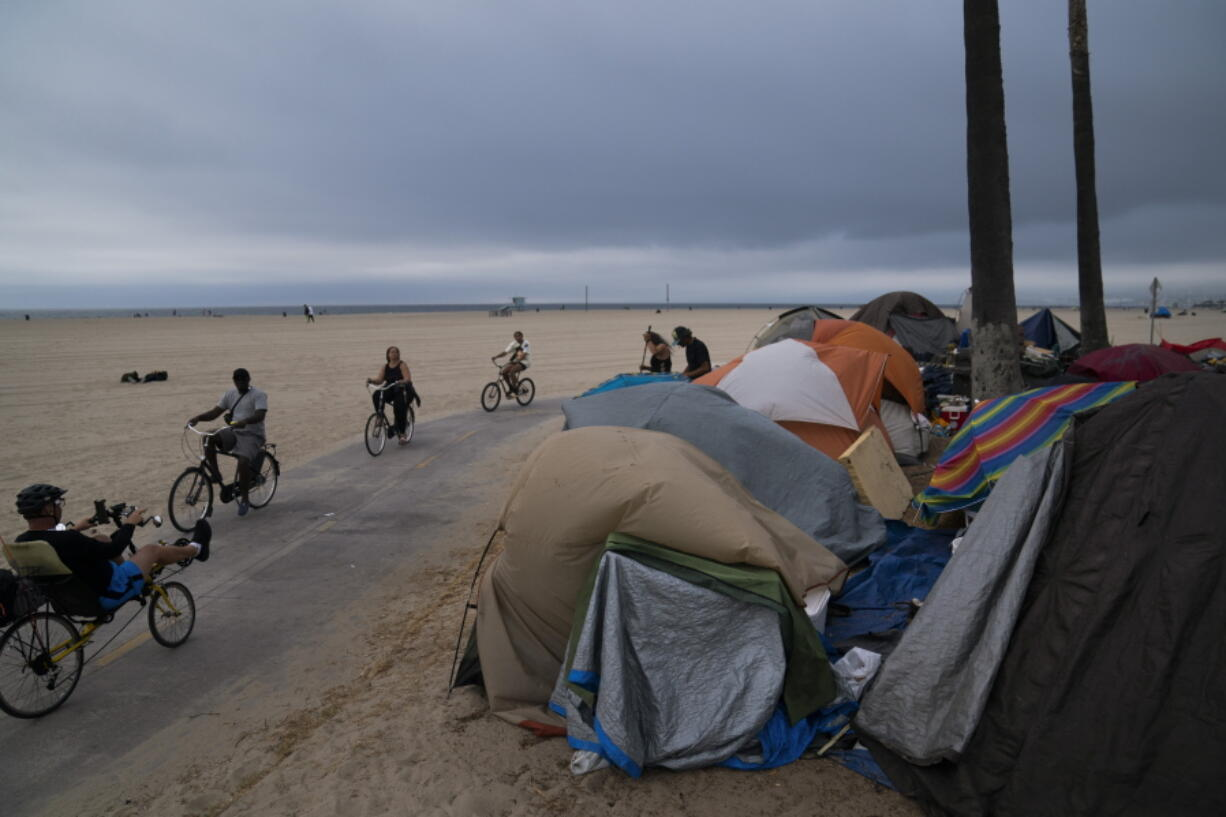 FILE - In this June 29, 2021, file photo people ride their bikes past a homeless encampment set up along the boardwalk in the Venice neighborhood of Los Angeles. The share of Americans living in poverty rose slightly as the COVID pandemic shook the economy last year, but massive relief payments pumped out by Congress eased hardship for many, the Census Bureau reported Tuesday, Sept. 14. The official poverty measure showed an increase of 1 percentage point in 2020, indicating that 11.4 percent of Americans were living in poverty. It was the first increase in poverty after five consecutive annual declines. (AP Photo/Jae C.
