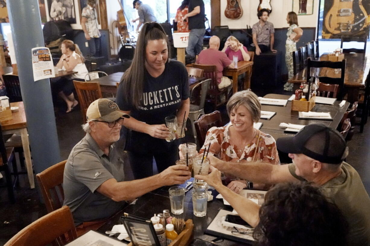 Macy Norman, center, serves a table of guests at Puckett's Grocery and Restaurant, Friday, Sept. 10, 2021, in Nashville, Tenn. In Nashville, tourism has come back faster than downtown office workers following COVID. Nashville's reputation as a tourist destination is buoying restaurants while businesses in other downtown areas have had to adapt as offices remained closed and workers stay home.