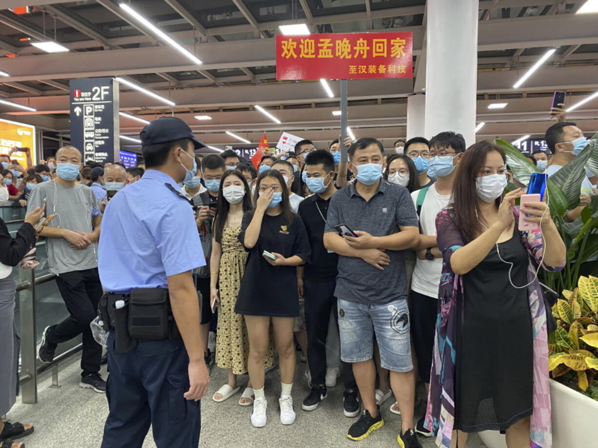 Police stand guard as supporters of Huawei CFO Meng Wanzhou gather at Shenzhen Bao'an International Airport in Shenzhen in southern China's Guangdong Province, Saturday, Sept. 25, 2021. China's government was eagerly anticipating the return of a top executive from global communications giant Huawei Technologies on Saturday following what amounted to a high-stakes prisoner swap with Canada and the U.S.