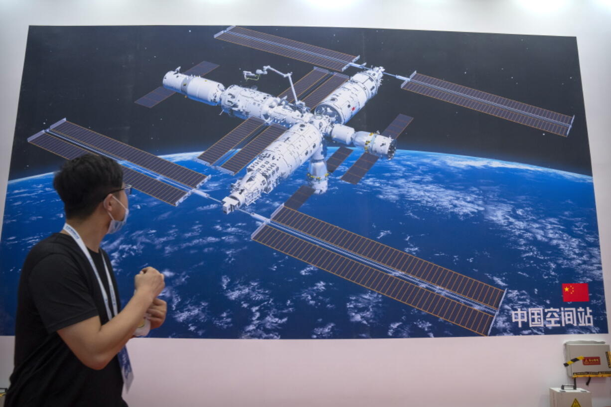A visitor looks at a mural showing an artist's rendering of China's space station at the World Robot Conference in Beijing, Saturday, Sept. 11, 2021. Three Chinese astronauts have departed from the country's orbiting space station in preparation for returning to Earth after 90 days in orbit, the national space agency reported Thursday, Sept. 16, 2021.