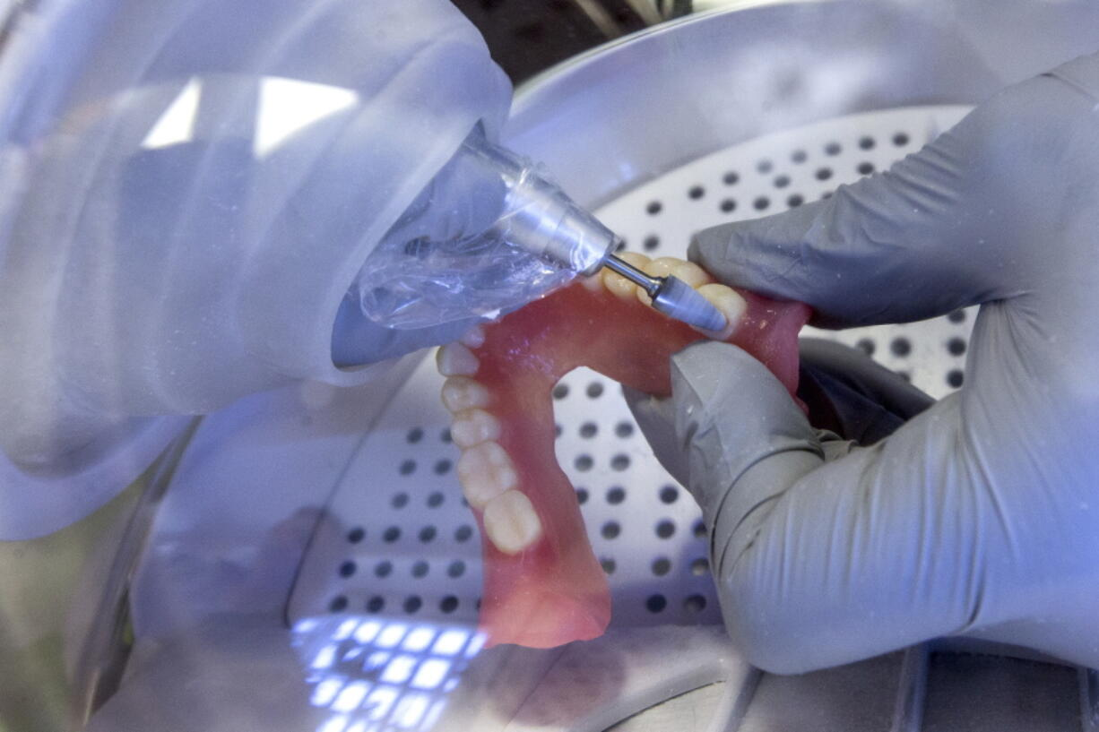 """FILE - In this June 13, 2019, file photo a dentist smooths out the edges of new 3D printed dentures in Huntsville, Texas. Dental work for Medicare recipients. An end to sky's-the-limit pricing on prescription drugs. Coverage for low-income people locked out of Medicaid because of political battles. Those are just some of the changes to health care that Democrats want to achieve with President Joe Biden's massive """"Build Back Better"""" plan."""