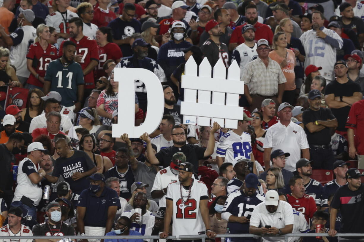 A Tampa Bay Buccaneers fan holds a sign during the first half of an NFL football game against the Dallas Cowboys Thursday, Sept. 9, 2021, in Tampa, Fla.