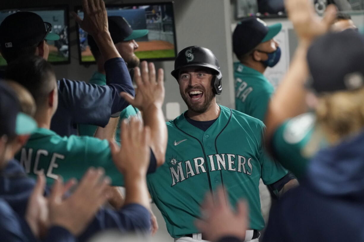 Seattle Mariners' Tom Murphy reacts in the dugout after hitting a two-run home run to also score Luis Torrens during the second inning of a baseball game against the Arizona Diamondbacks, Friday, Sept. 10, 2021, in Seattle. (AP Photo/Ted S.