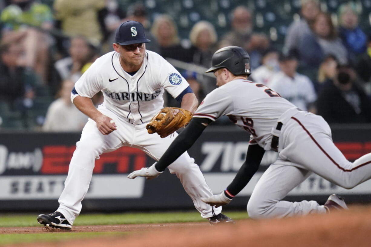 Arizona Diamondbacks' Pavin Smith, right, slides toward a tag by Seattle Mariners third baseman Kyle Seager during the fourth inning of a baseball game Saturday, Sept. 11, 2021, in Seattle. Smith was out on the double play, along with Nick Ahmed, who flied out.