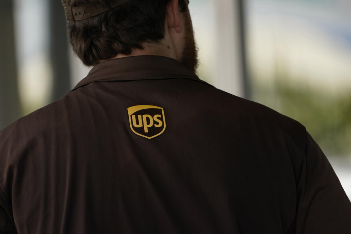 A UPS logo is on the shirt of a driver as he enters a United Parcel Service store with packages in Jackson, Miss., Monday, July 26, 2021.   Amazon, Chobani, UPS and more than 30 other companies have vowed to hire and train refugees fleeing Afghanistan for the U.S. The companies said Tuesday, Sept. 21,  that they want to help the tens of thousands of Afghan refugees coming to America to integrate into the economy.   (AP Photo/Rogelio V.