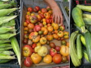 From left, corn, tomatoes and zucchini displayed at a farmers market in Milford, Conn.