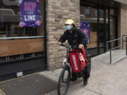 FILE - In this April 21, 2021 file photo, a delivery man bikes with a food bag from Grubhub in New York.  The three biggest food delivery companies, DoorDash, Grubhub and Uber Eats, are suing the City of New York, Friday, Sept.