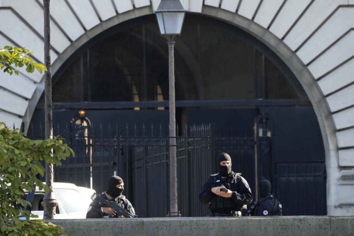 Security forces guard an entrance of the Palace of Justice Wednesday, Sept. 8, 2021 in Paris. France is putting on trial 20 men accused in the Islamic State group's 2015 attacks on Paris that left 130 people dead and hundreds injured. The proceedings begin Wednesday in an enormous custom-designed chamber. Most of the defendants face the maximum sentence of life in prison if convicted of complicity in the attacks. Only Abdeslam is charged with murder.