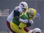 Oregon quarterback Anthony Brown (13) is wrapped up by Fresno State tackle Leonard Payne (55) and defensive end Aaron Mosby (3) during the first quarter of an NCAA college football game, Saturday, Sept. 4, 2021, in Eugene, Ore.