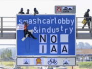 """An activist hangs from a gantry over the A9 motorway near F?rholzen in the direction of Munich during a banner campaign, holding a banner with the words """"Destroy cars"""" in his hands while police officers from a special task force get into position on the gantry, Tuesday, Sept.7, 2021. The activists have pasted over the traffic sign with the words """"smashcarlobby & industry - NO IAA""""."""