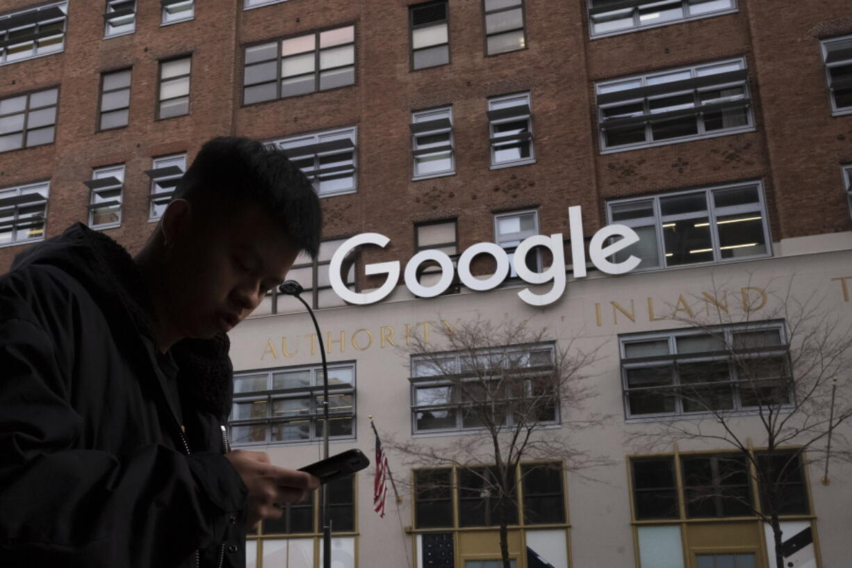 FILE - In this file photo dated Monday, Dec. 17, 2018, a man using a mobile phone walks past Google offices in New York. Google is planning to buy New York's St.  John's Terminal for $2.1 billion, making it the anchor of its Hudson Square campus.