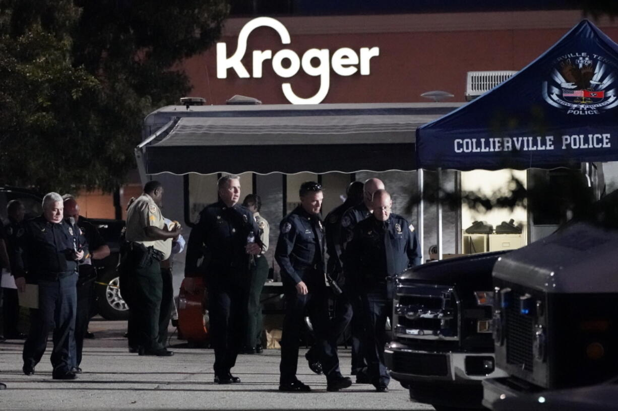 Law enforcement personnel work in front of a Kroger grocery store as an investigation goes into the night following a shooting earlier in the day on Thursday, Sept. 23, 2021, in Collierville, Tenn. Police say a gunman attacked people in the store and killed at least one person and wounded 12 others before the suspect was found dead.