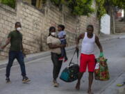 Jean Charles Celestin, right, carries luggage belonging to his cousin Jhon Celestin, left, Jhon's wife Delta De Leon, and their daughter Chloe, in Port au Prince, Haiti, Wednesday, Sept. 22, 2021. Jhon Celestin arrived in Haiti aboard the last flight Wednesday to the Haitian capital, a city the 38-year-old left three years ago in search of a better-paying job to help support his family.