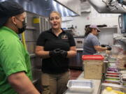 Sarah White, center, area manager of Lost Dog Cafe, trains manager Alex Aleman, left, in a new pasta preparation technique, as they work Aug. 27 at the cafe in Fairfax, Va.