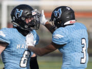 Hockinson's Ty Litle gets a pat on the head from Kenyon Johnson after his second sack sealed the Hawks' victory over Ridgefield on Saturday, March 13, 2021, at District Stadium in Battle Ground. Hockinson won 14-7 in the game between the 2A Greater St. Helens League's top two teams.