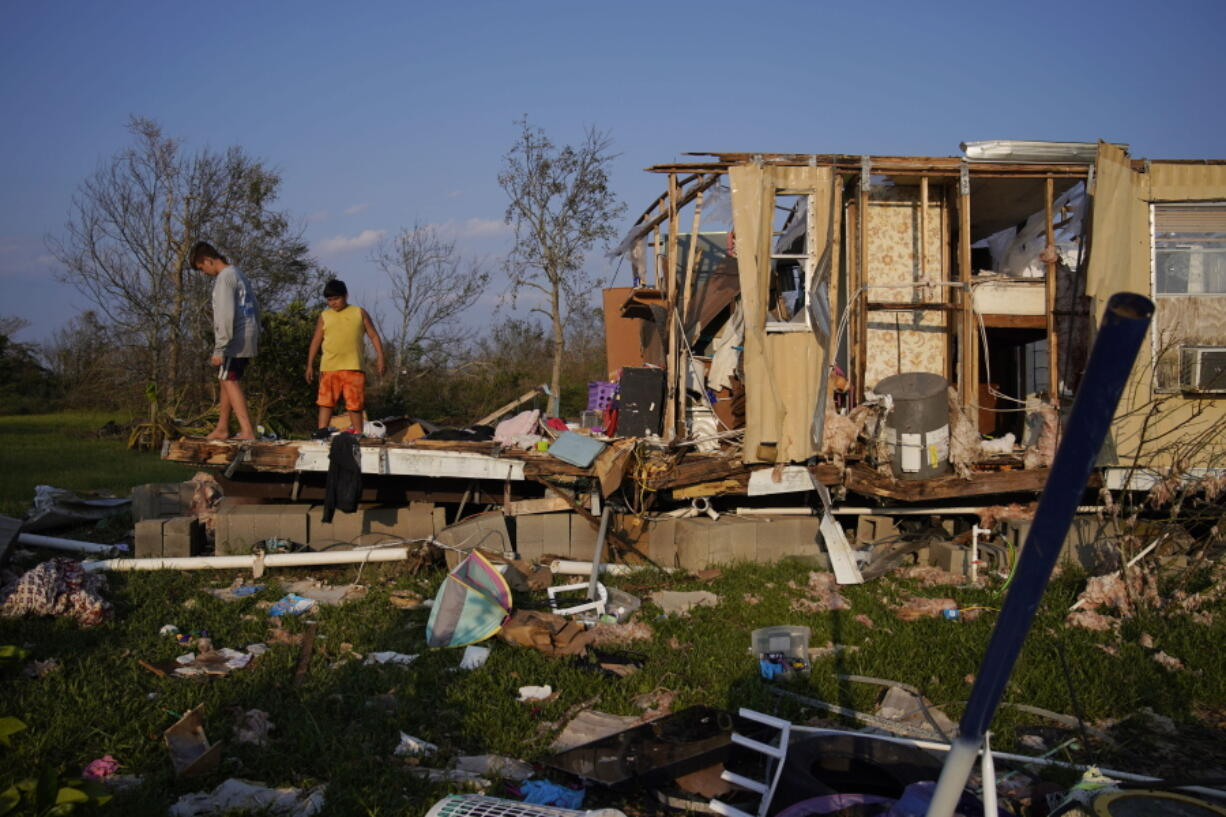 FILE - In this Sept. 4, 2021 file photo, Aiden Locobon, left, and Rogelio Paredes look through the remnants of their family's home destroyed by Hurricane Ida in Dulac, La.  Louisiana students, who were back in class after a year and a half of COVID-19 disruptions kept many of them at home, are now missing school again after Hurricane Ida. A quarter-million public school students statewide have no school to report to, though top educators are promising a return is, at most, weeks away, not months.