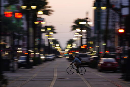 In the aftermath of Hurricane Ida, a man rides his bike across Canal Street, Saturday, Sept. 4, 2021, in the French Quarter of New Orleans.