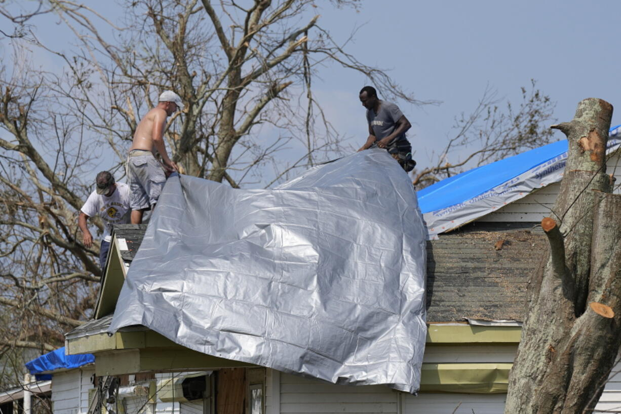 Gary Johnston, left, Grant Boughamer, center, and Jose Garcia, right, place a tarp on a roof damaged by Hurricane Ida, Thursday, Sept. 2, 2021, in Golden Meadow, La. (AP Photo/David J.