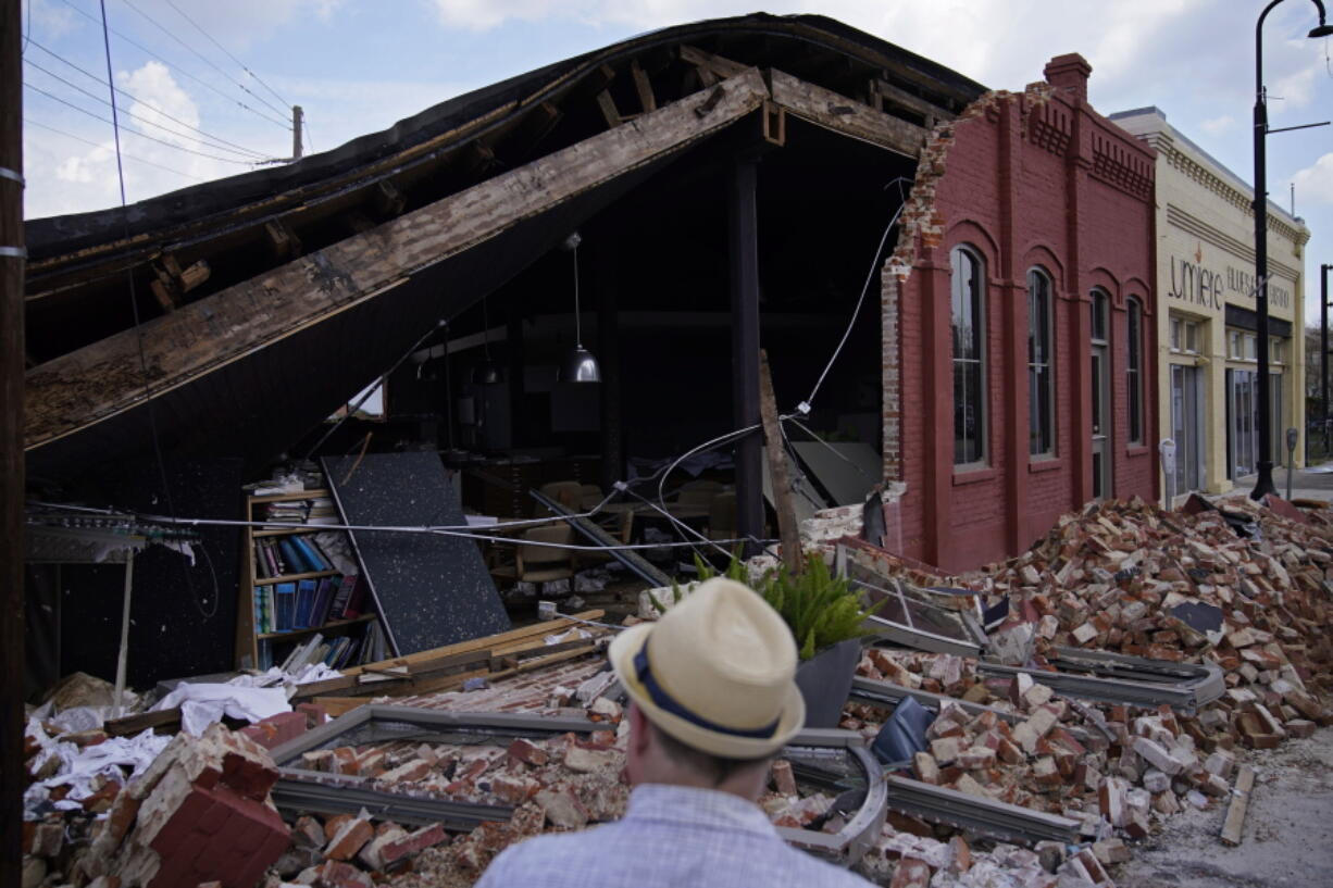 A man looks at a partially collapsed building Saturday in Houma, La.