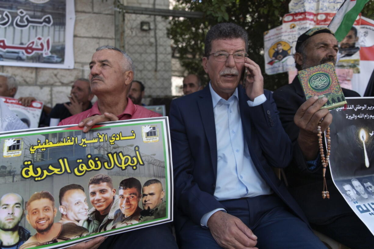 """Qadoura Fares, center, attends a protest supporting prisoners, while a fellow protester carries a poster with pictures of the six Palestinian prisoners who escaped from an Israeli jail that says """"heroes of the freedom tunnel,"""" in the West Bank city of Ramallah, Tuesday, Sept. 14, 2021."""