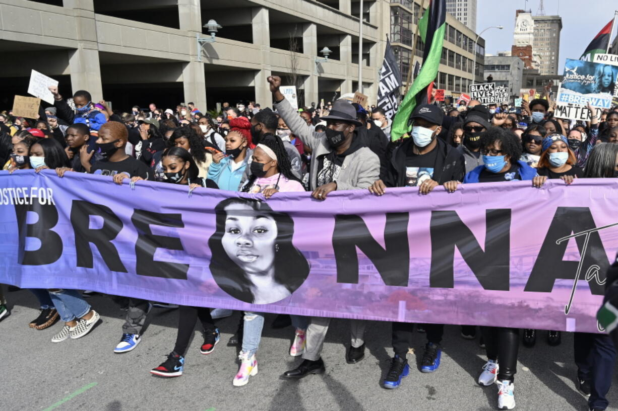"""FILE - In this March 13, 2021 file photo, Tamika Palmer, center, the mother of Breonna Taylor, leads a march through the streets of downtown Louisville on the one year anniversary of her death in Louisville, Ky. The Justice Department said Tuesday, Sept. 14, it is curtailing federal agents' use of so-called """"no-knock"""" warrants -- which allow law enforcement agents to enter a home without announcing their presence -- and would also prohibit its agents from using chokeholds in most circumstances. The updated policy follows the March 2020 death of Breonna Taylor, who was shot and killed by police in her home during a no-knock warrant and whose death led to months of mass protests over racial injustice in policing and the treatment of Black people in the United States. (AP Photo/Timothy D."""