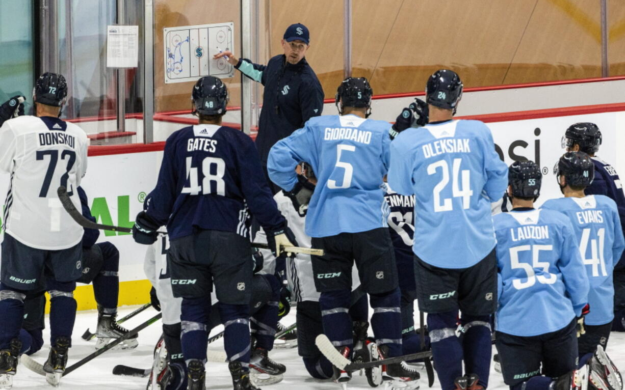 Seattle Kraken head coach Dave Hakstol goes over a drill with players during NHL hockey training camp at Kraken Community Iceplex on Thursday, Sept. 23, 2021, in Seattle.