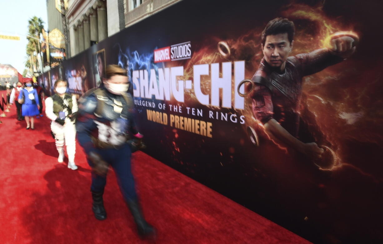 """Fans dressed as Marvel characters attend the premiere of """"Shang-Chi and the Legend of the Ten Rings"""" on Monday, Aug. 16, 2021, at the El Capitan Theatre in Los Angeles."""
